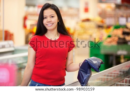 Smiling woman holding product in shopping centre and looking at camera - stock photo