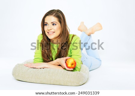 Smiling woman holding red apple lying on a floor with crossed legs. Big toothy smile. White background isolated. - stock photo