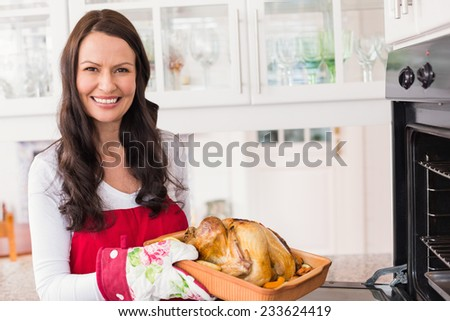 Smiling woman holding roast turkey at home in the kitchen - stock photo