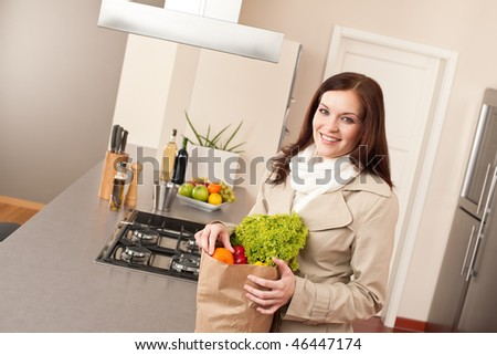 Smiling woman holding shopping bag with grocery in kitchen