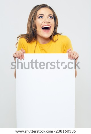 smiling woman holding sign card looking up. studio isolated portrait of beautiful girl. - stock photo