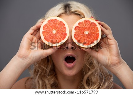 Smiling woman holding two grapefruits in hands - stock photo