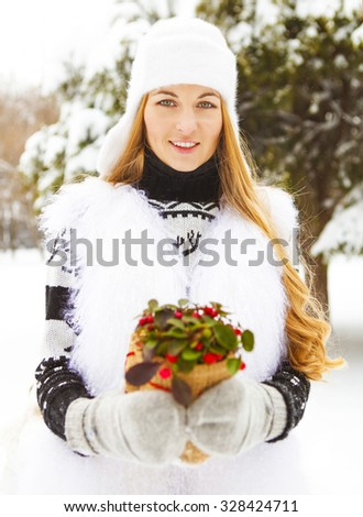 Smiling woman holding winter plant in her hands. Close up - stock photo