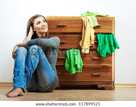 Smiling woman home portrait isolated against white. Young model seating at cupboard for clothes. - stock photo