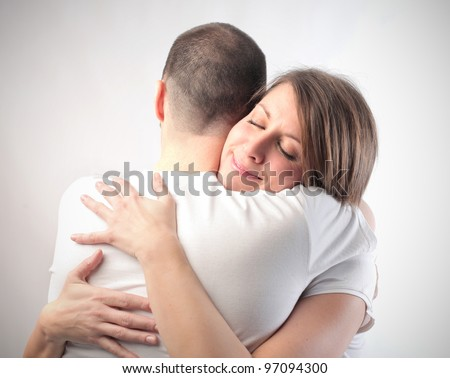 Smiling woman hugging her husband - stock photo
