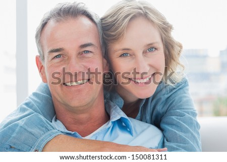 Smiling woman hugging her husband on the couch from behind at home in the living room - stock photo