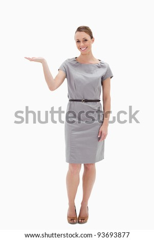 Smiling woman in a dress presenting something with her hand against white background - stock photo