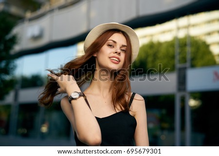 Smiling woman in a hat straightens her hair on the background of a building, evening
