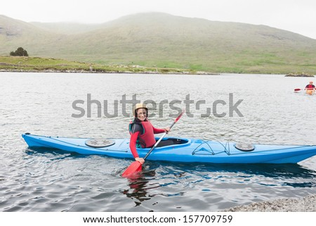 Smiling woman in a kayak in a lake looking at camera - stock photo