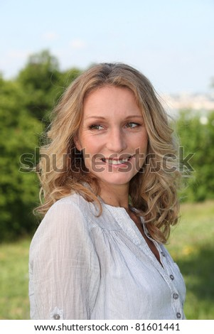 Smiling woman in a park - stock photo