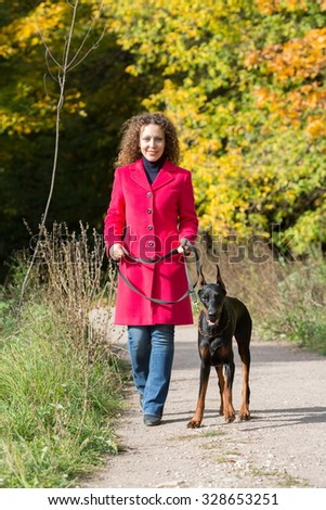 Smiling woman in a red coat is walking with the dobermann.