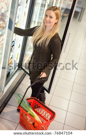 Smiling woman in a supermarket standing in front of the cooler looking at camera - stock photo