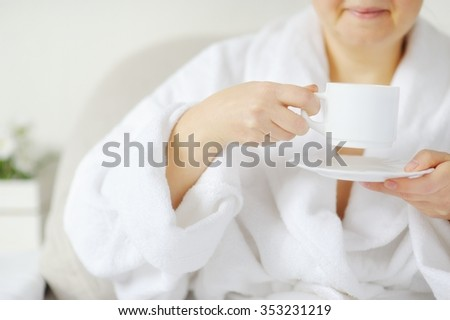 Smiling woman in a white coat at the table drinking a hot drink