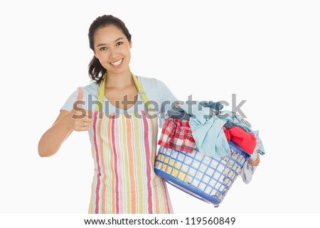 Smiling woman in apron carrying laundry basket and giving thumbs up - stock photo