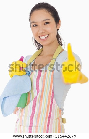 Smiling woman in apron holding cleaning products giving thumbs up - stock photo