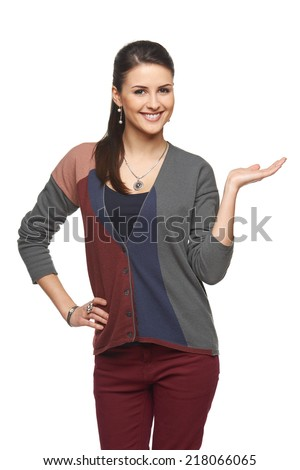 Smiling woman in autumn cardigan showing open hand palm with copy space for product or text - stock photo