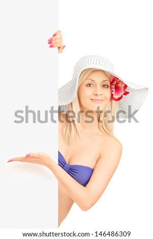 Smiling woman in bikini standing and gesturing on a blank panel isolated on white background - stock photo