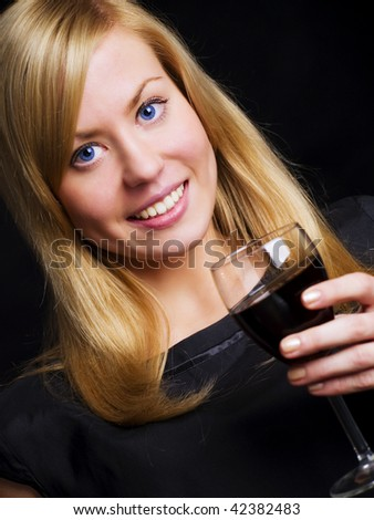 smiling woman in black dress holding wine and celebrating - stock photo