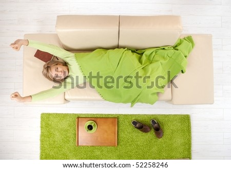 Smiling woman in blanket stretching on living room couch after nap, coffee on tray. - stock photo