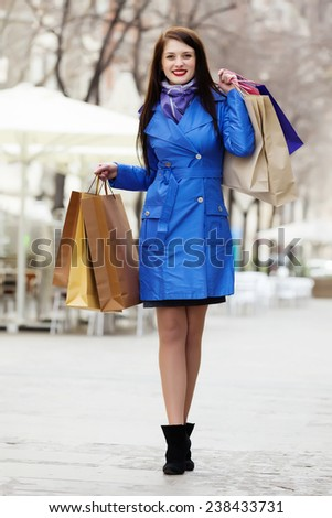 Smiling woman in blue cloak with purchases at street