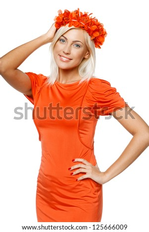 Smiling woman in bright orange dress holding the orange wreath on her head, over white background