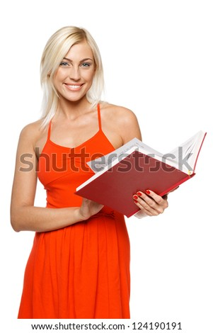 Smiling woman in bright red dress turning the pages of a book over white background