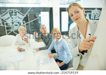 Smiling woman in business meeting in conference room on a whiteboard - stock photo