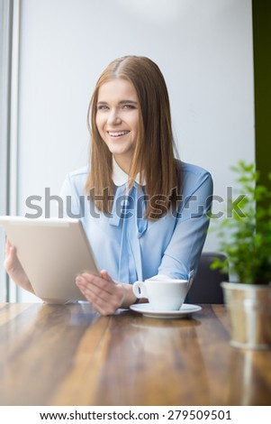 Smiling woman in cafe with digital tablet