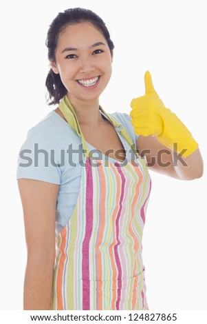Smiling woman in cleaning clothes giving thumbs up - stock photo