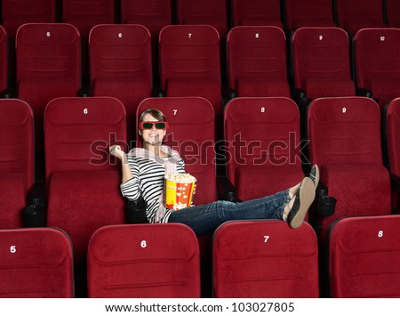 Smiling woman in 3D movie theater sitting alone in the row - stock photo