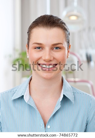 smiling woman in dentist office showing perfect teeth - stock photo