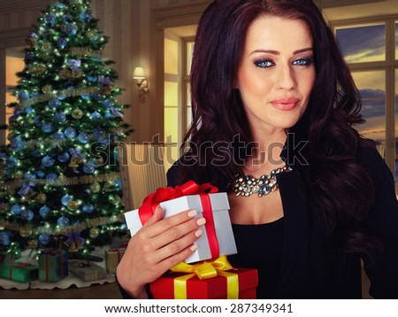 smiling woman in dress holding red gift box over christmas tree lights background - stock photo