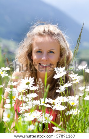 Smiling woman in field of chamomiles - stock photo