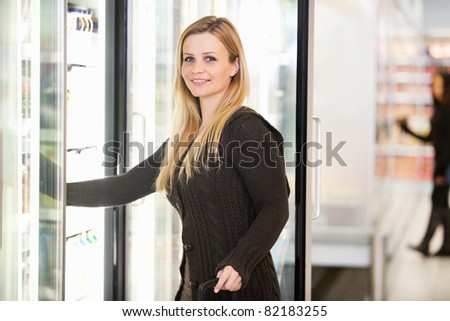 Smiling woman in front of refrigerator looking at camera with person in the background - stock photo