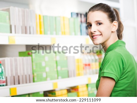 Smiling woman in green polo shirt shopping at store rear view. - stock photo
