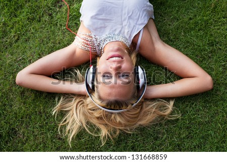 smiling woman in headphones on the grass - stock photo
