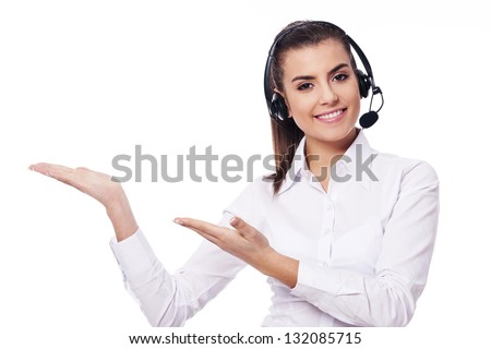 Smiling woman in headset showing something - stock photo