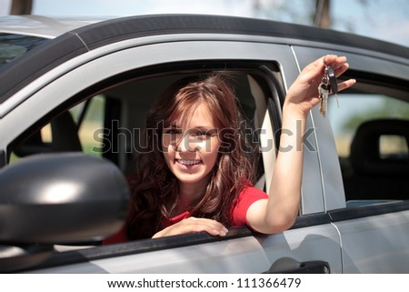 Smiling woman in her new car showing keys