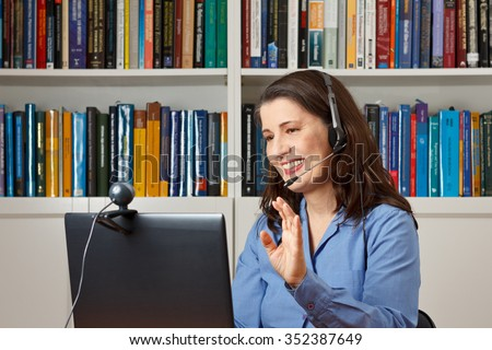 Smiling woman in her office with laptop, camera and headset telephoning with her children via the internet - stock photo