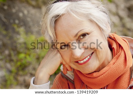 smiling woman in her 60s outdoors - stock photo