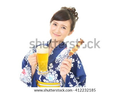 Smiling woman in Japanese summer kimono eating Yakitori