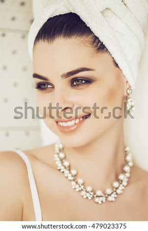 Smiling woman in jewelry with pearls and towel on head in bathroom