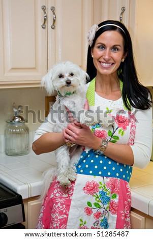 Smiling woman in kitchen holding cute white Maltese dog - stock photo
