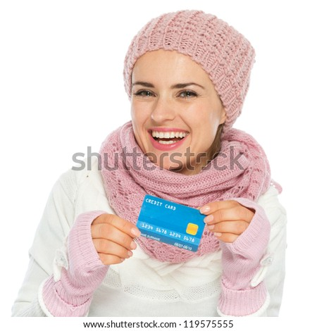 Smiling woman in knit scarf, hat and mittens holding credit card - stock photo