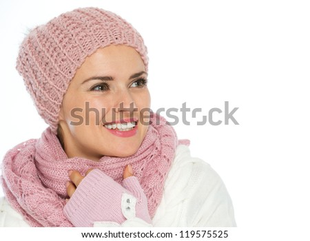 Smiling woman in knit scarf, hat and mittens looking on copy space