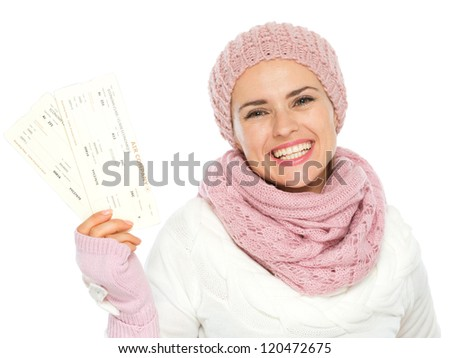 Smiling woman in knit winter clothing holding air tickets - stock photo
