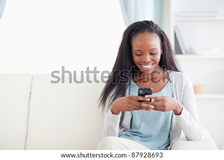 Smiling woman in living room reading text message