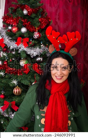 Smiling woman in red and green clothes wearing Reindeer ears and standing near Xmas tree - stock photo