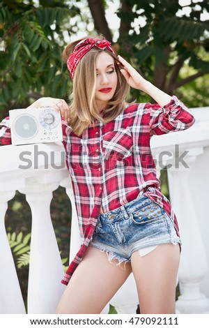 Smiling woman in red bandana and a plaid shirt. Beautiful girl with pretty smile holding retro tape recorder