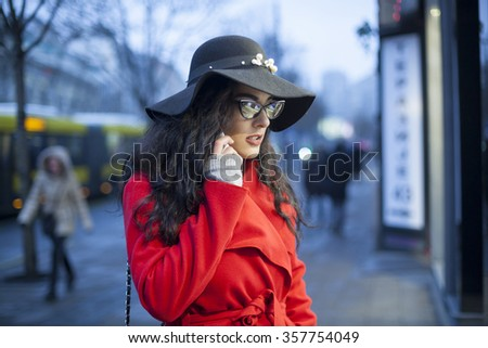 Smiling Woman in Red Coat and black hat and glasses, hold smartphone, Woman in red coat with smartphone in hands going through the city and looking shop windows. Urban Space, noise on image - stock photo